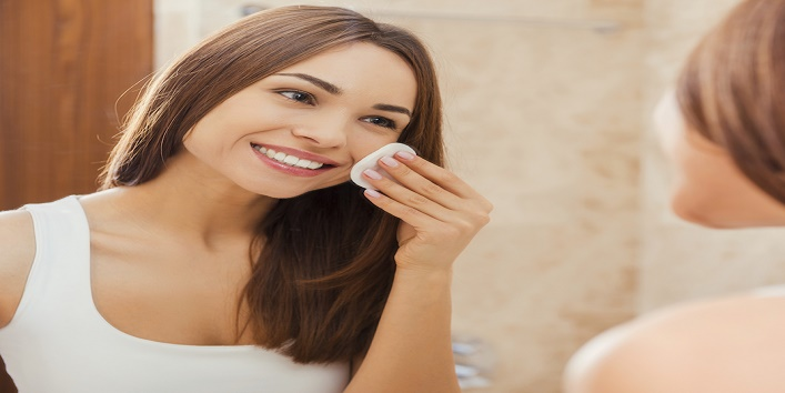 Staying fresh and clean. Beautiful young woman touching her face with sponge and smiling while standing in front of the mirror